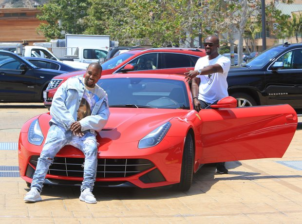 Kanye West poses against red Ferrari on lunch date