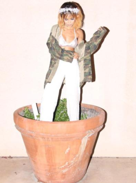 Jhene Aiko standing in plant pot